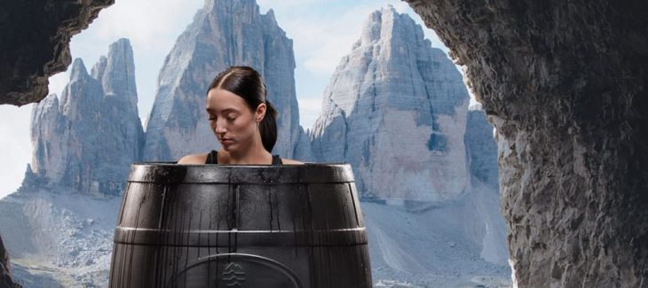 a woman sits in an ice barrel to do cold water therapy
